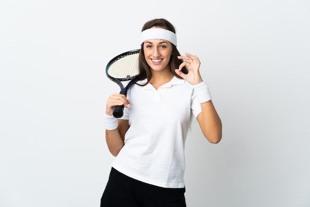 Молодая женщина-теннисистка над изолированной белой стеной, показывая пальцами знак ок