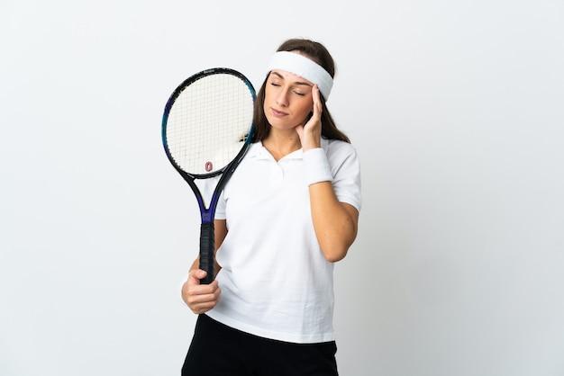 Молодая женщина-теннисистка над изолированной белой стеной с головной болью