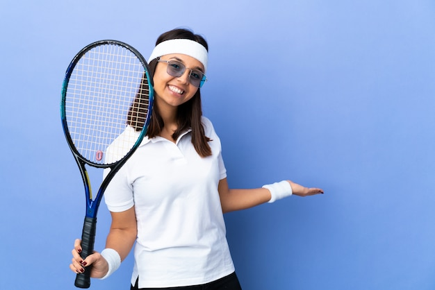 Young woman tennis player over wall extending hands to the side for inviting to come