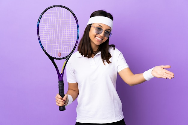 Young woman tennis player over wall presenting and inviting to come with hand