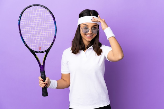 Young woman tennis player over wall saluting with hand with happy expression
