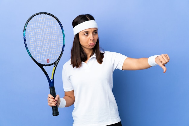 Young woman tennis player over wall showing thumb down with negative expression