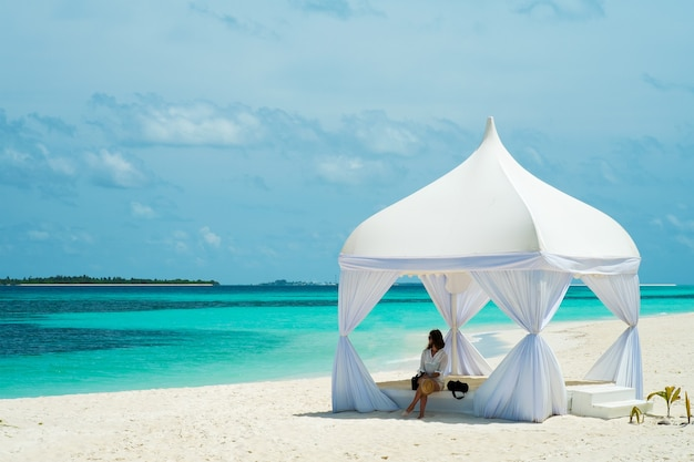 Young woman in a tent on the shores of the azure ocean
