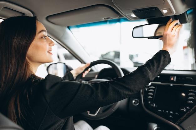 若い女性が車のショールームで車をテスト