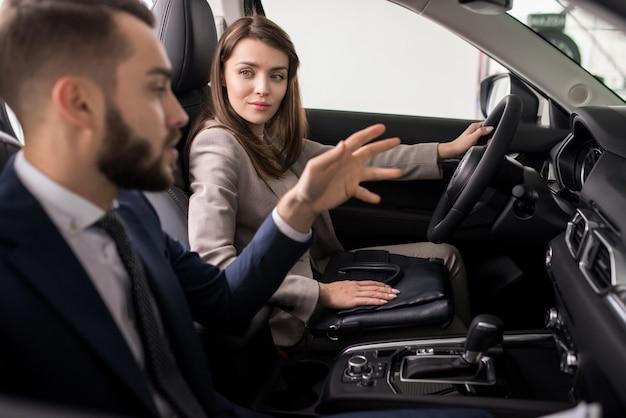 Молодая женщина тестирует новый автомобиль в автосалоне
