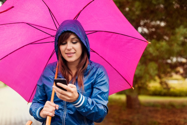Giovane donna che manda un sms sul cellulare sotto la pioggia