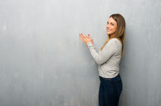 Young woman on textured wall applauding after presentation in a conference