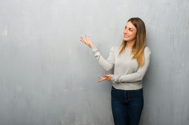 Young woman on textured wall extending hands to the side for inviting to come