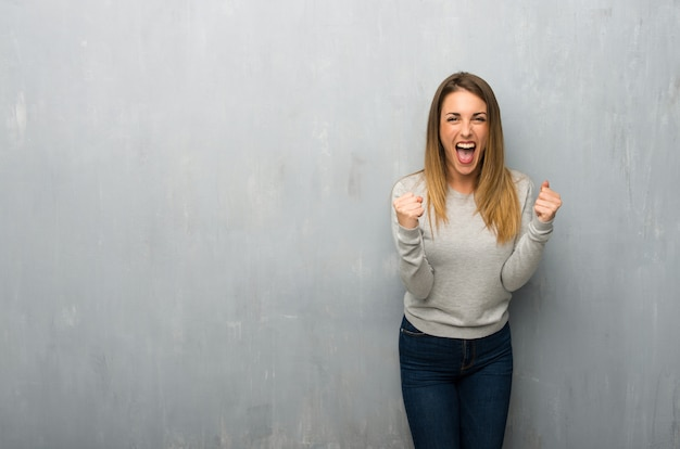 Young woman on textured wall frustrated by a bad situation