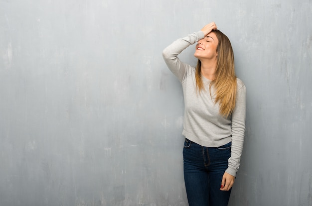 Young woman on textured wall has just realized something and has intending the solution