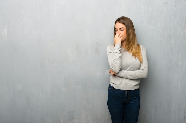 Young woman on textured wall having doubts