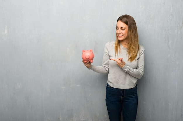 Young woman on textured wall holding a piggybank