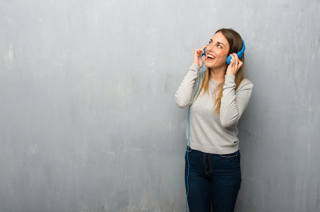 Young woman on textured wall listening to music with headphones