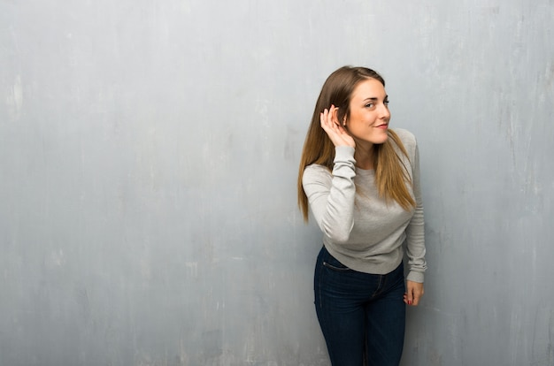 Young woman on textured wall listening to something by putting hand on the ear