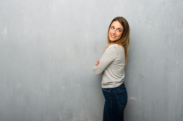 Young woman on textured wall looking over the shoulder with a smile