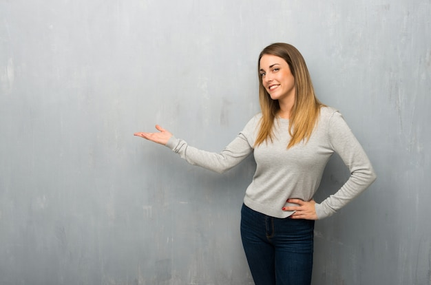Young woman on textured wall pointing back and presenting a product