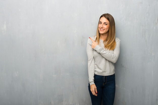 Young woman on textured wall pointing to the side to present a product