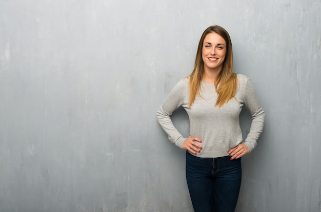 Young woman on textured wall posing with arms at hip and laughing looking to the front