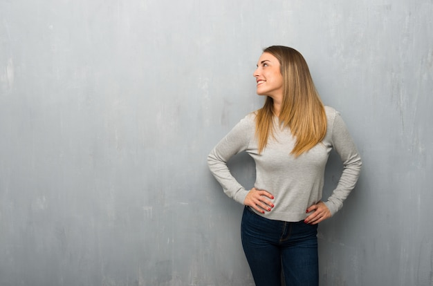 Young woman on textured wall posing with arms at hip and laughing
