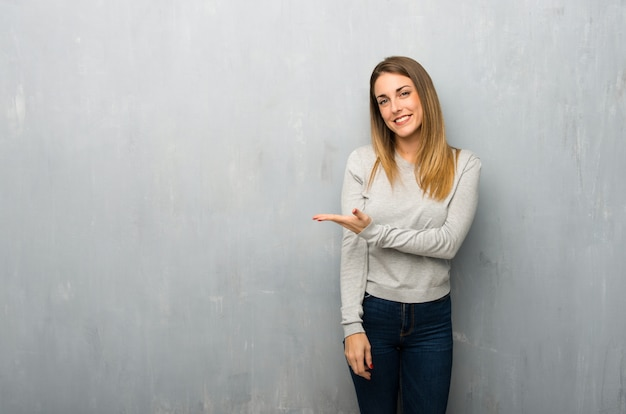 Young woman on textured wall presenting an idea while looking smiling towards