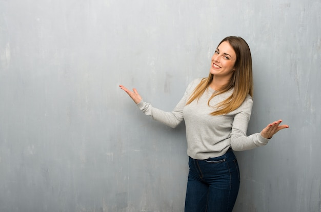 Young woman on textured wall proud and self-satisfied in love yourself concept