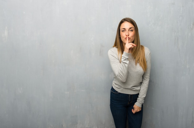 Young woman on textured wall showing a sign of silence gesture putting finger in mouth
