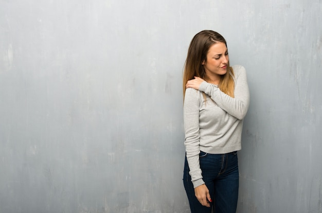 Young woman on textured wall suffering from pain in shoulder for having made an effort