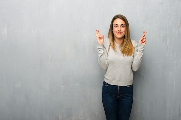 Young woman on textured wall with fingers crossing and wishing the best