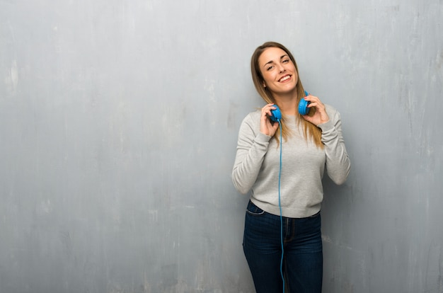 Young woman on textured wall with headphones
