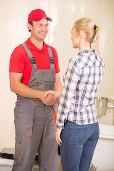 Young woman thanks for plumbing work in the bathroom.