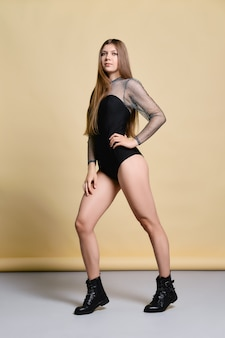 Young woman in thight body suit and rough boots posing in studio over pale yellow