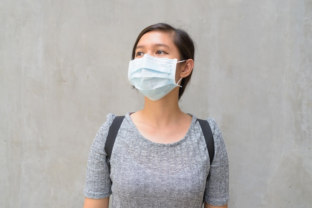 屋外でコロナウイルスの発生から保護するためのマスクを考えて身に着けている若い女性