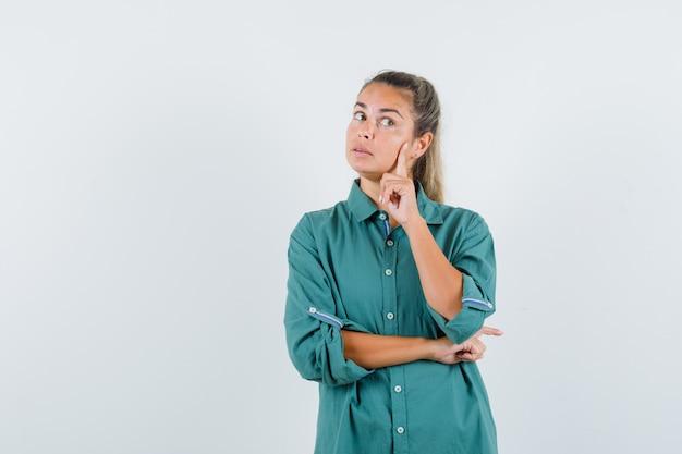 Молодая женщина думает в синей рубашке и смотрит задумчиво