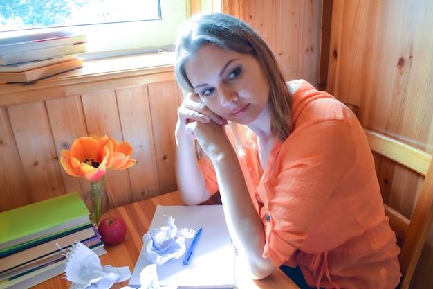 本を考えている若い女性。テーブルの上の本を考えている女性。難しい試験課題。
