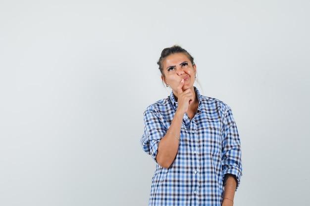 Молодая женщина что-то думает, скучая по лицу в клетчатой рубашке и выглядит сосредоточенной.
