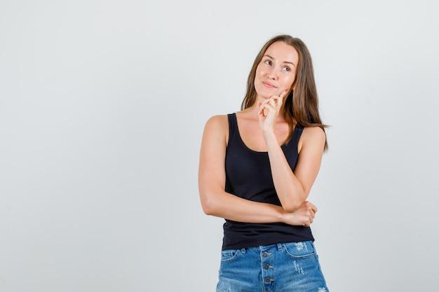 Giovane donna che pensa mentre distoglie lo sguardo in singoletto, pantaloncini e sembra allegra. vista frontale.