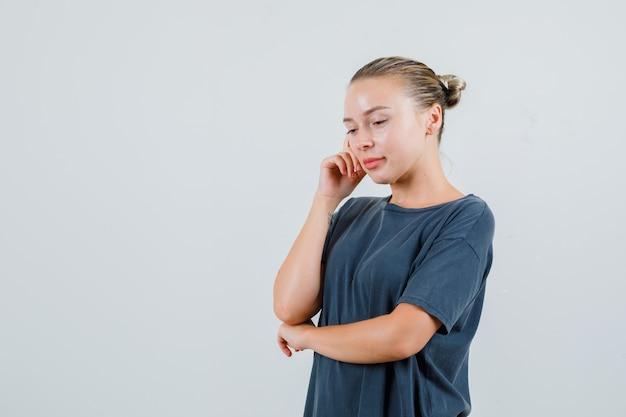 Giovane donna che pensa mentre guarda in t-shirt grigia e sembra speranzosa