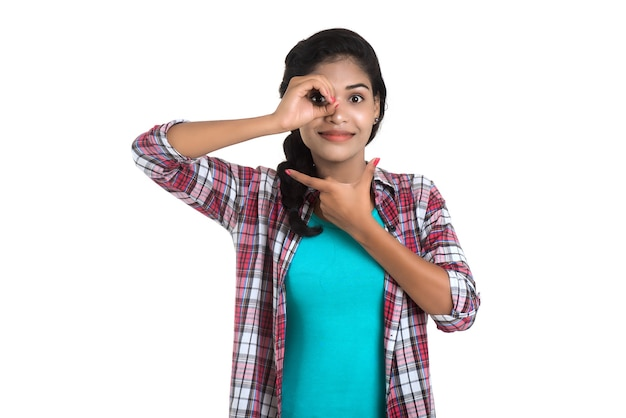 Young woman through fingers in ok gesture. imitating binoculars over white wall