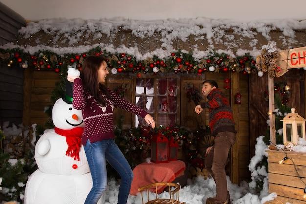 雪だるまとさまざまな美しいクリスマスの装飾と木造住宅の中で遊んでいる間、彼女のパートナーに綿の雪を投げる若い女性。