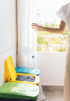 ペットボトルを黄色い容器に投げる若い女性