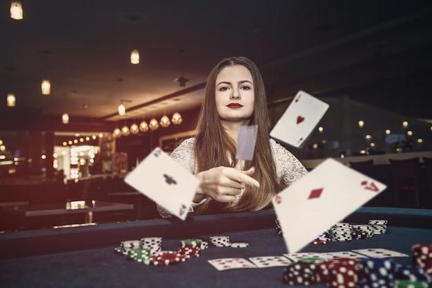 카지노에서 카드 놀이를 던지는 젊은 여자
