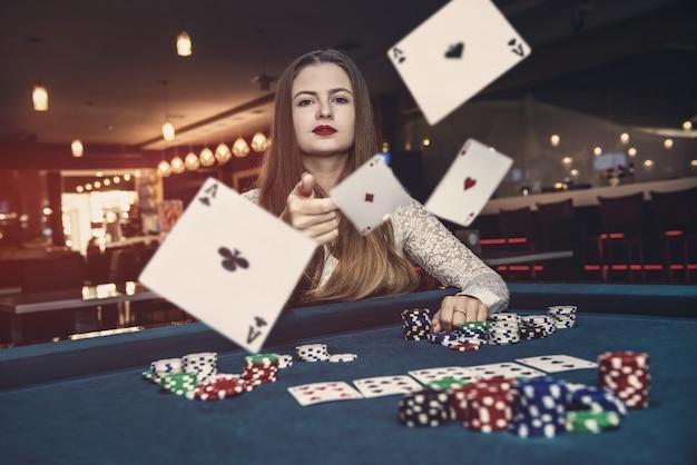 카지노에서 카드 놀이를 던지는 젊은 여자 프리미엄 사진