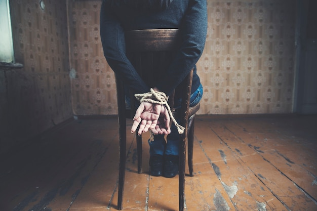 Young woman tied to chair