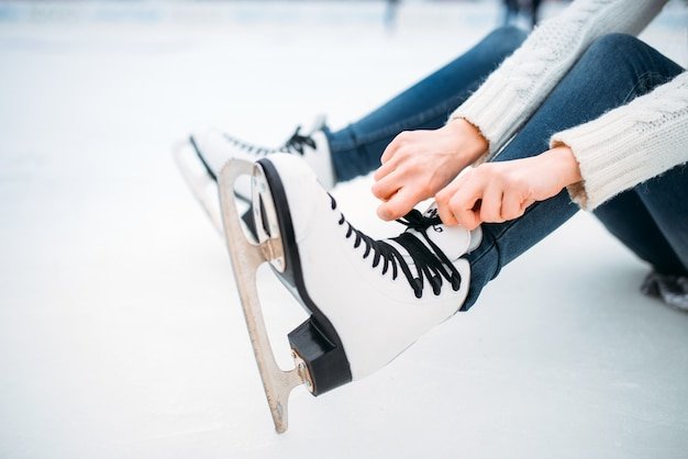 Young woman ties the shoelaces on skates