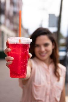 Giovane donna che tollera l'ondata di caldo con una bevanda fresca