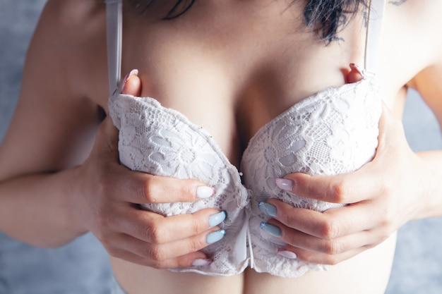 Молодая женщина трогает свою грудь в бюстгальтерах на сером фоне