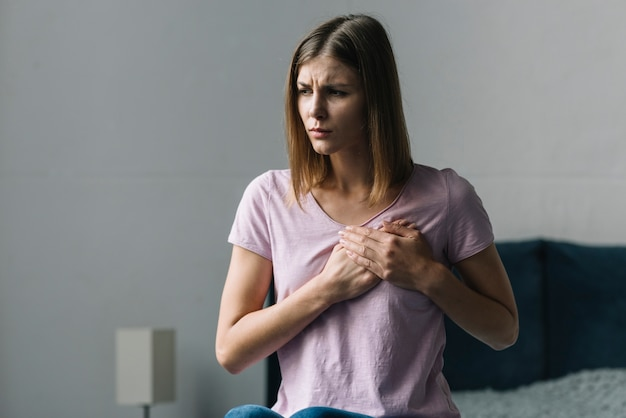 Young woman touching her chest in pain at home