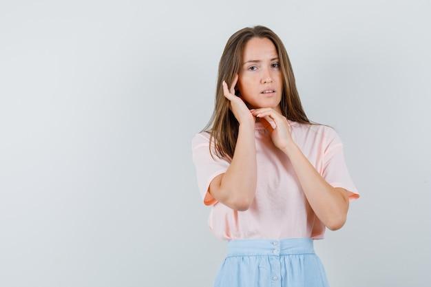 Tシャツ、スカートの正面図で彼女の耳に触れる若い女性。