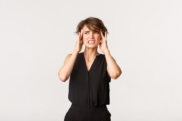 こめかみに触れ、痛みを伴う片頭痛から顔をゆがめた若い女性。頭痛を訴える少女、白く立っている。