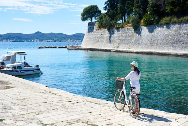 Молодая женщина турист байкер с городской велосипед в городе у моря
